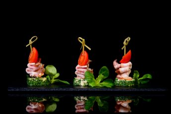 canapes bacon tomato on black background with reflection